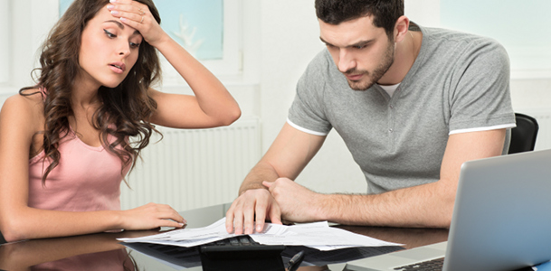 Distraught Young Couple With Bills